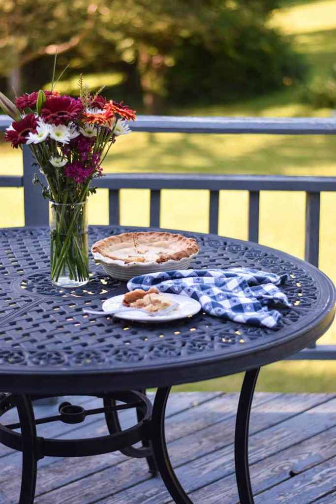 Picnic Table with Pineapple Pie, bouquet of flowers and green backyard scene