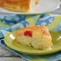 Pineapple Upside-Down Cake on neon green plate with blue and yellow napkin with cake serving platter in background