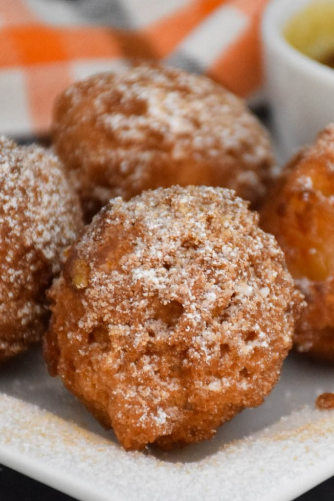 A white plate with homemade Apple Fritters that are dusted with confectioner sugar sprinkled on top.