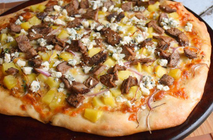 Whole Steak and Potato Pizza ona pizza stone