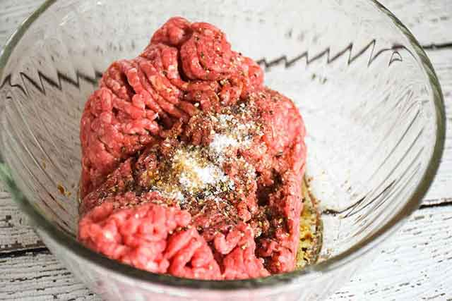 ground beef in a clear mixing bowl with seasonings on top