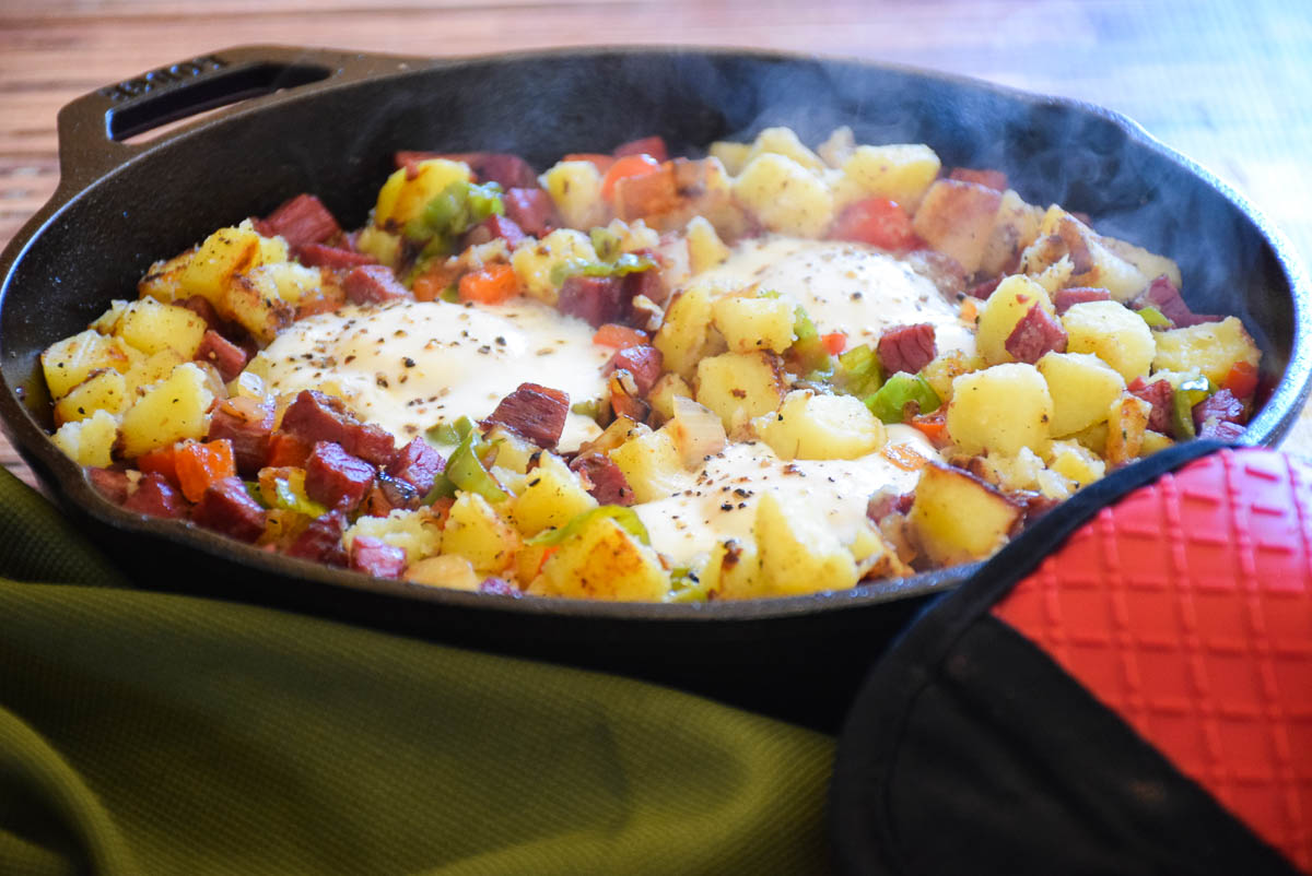 Cooked Homemade Corned Beef Hash and Eggs with steam coming out of hot cast iron skillet.