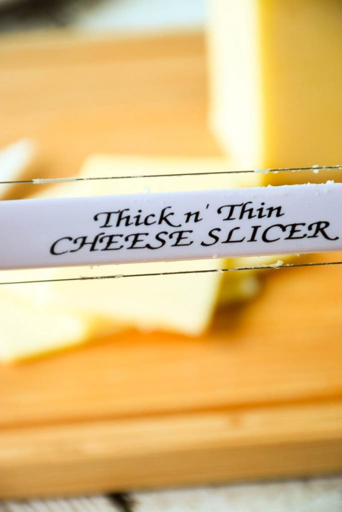 photo of thick and thin cheese slicer with sliced cheese in the background