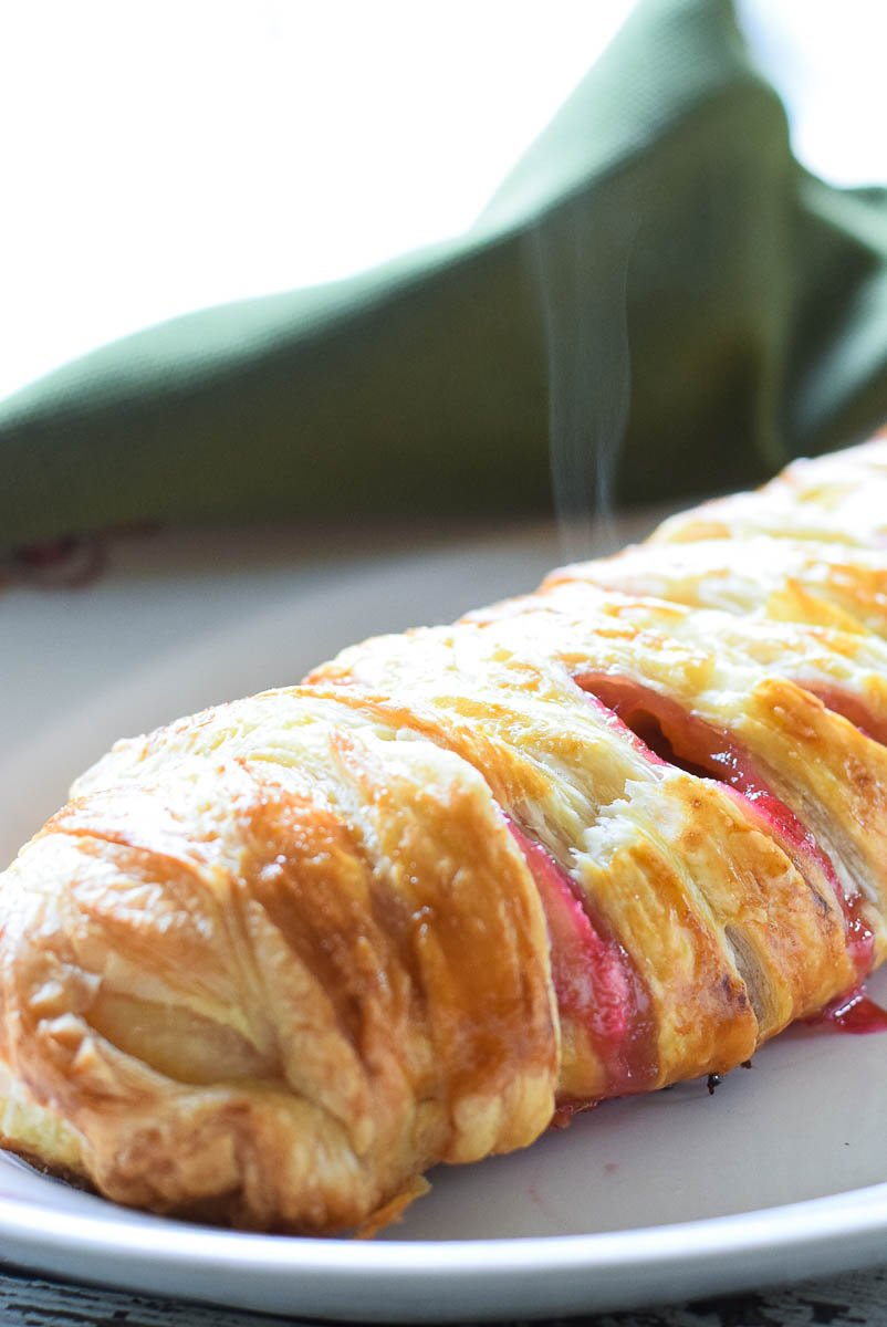 A Rhubarb Cheese Danish cooling on parchment paper with steam rising out of the danish