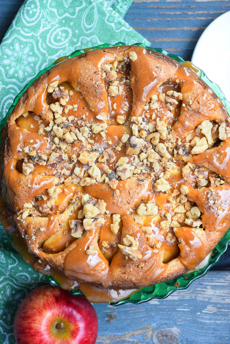 Overhead shot of a baked cake topped with caramel and walnuts on a green platter.
