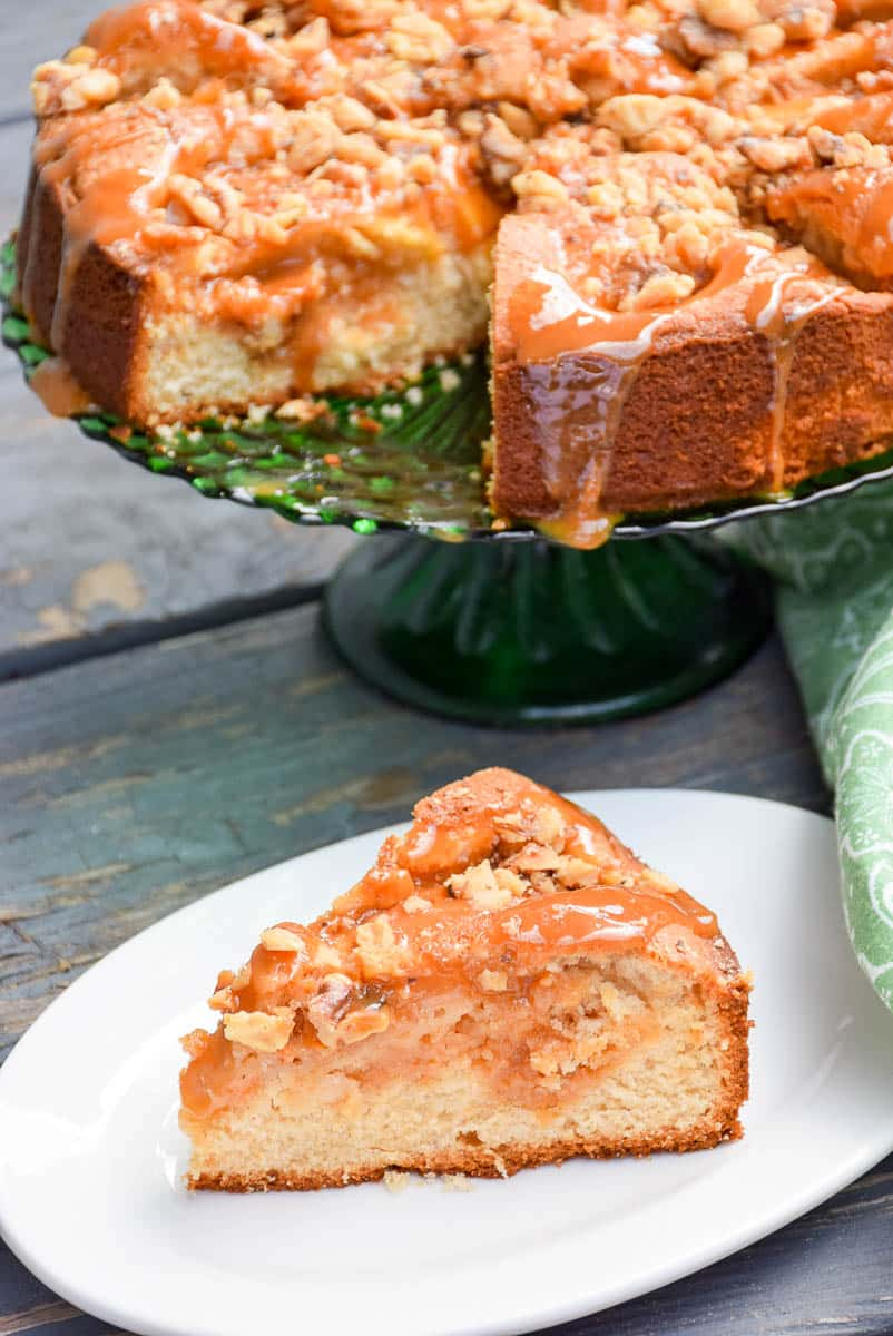 A slice of caramel apple cake with salted caramel and toasted walnut topping with the whole cake blurred in the background.