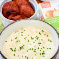 Quick and Easy Caramelized Onion Dip with baked salami chips in the background