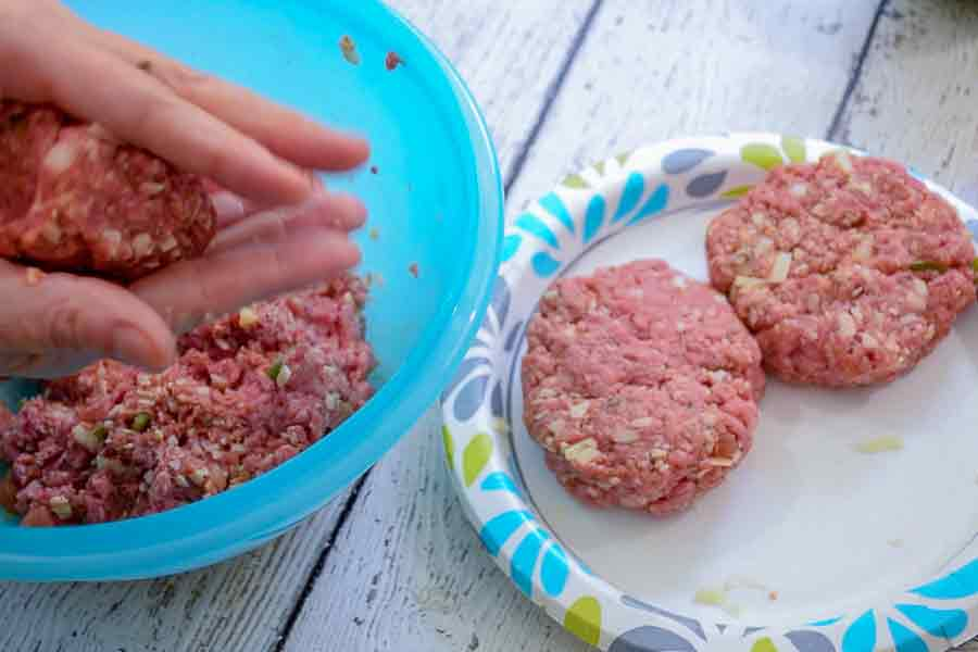 A pair of hands shaping ground beef into hamburgers 2 formed burgers on a plate