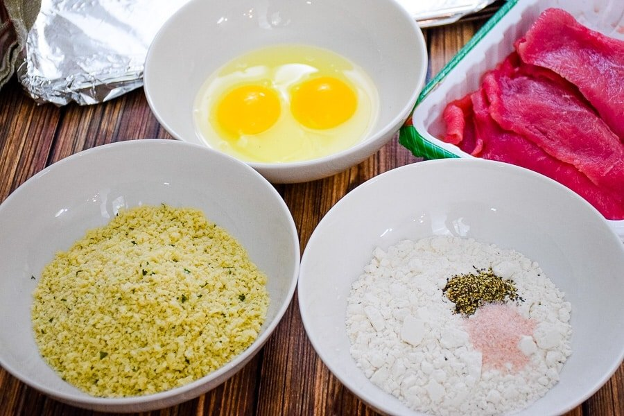 Meat, breadcrumbs, eggs, and flour, salt and pepper lined up for breading