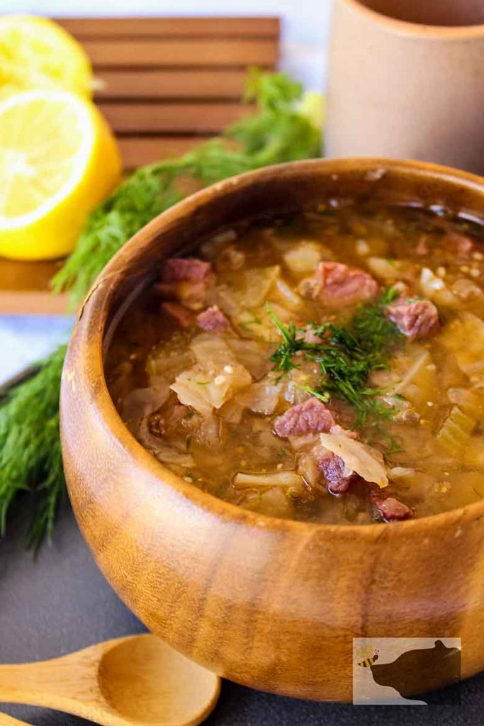 Upclose image of Corned Beef and Cabbage soup with fennel frond garnish and sliced lemon and fronds in the backbround