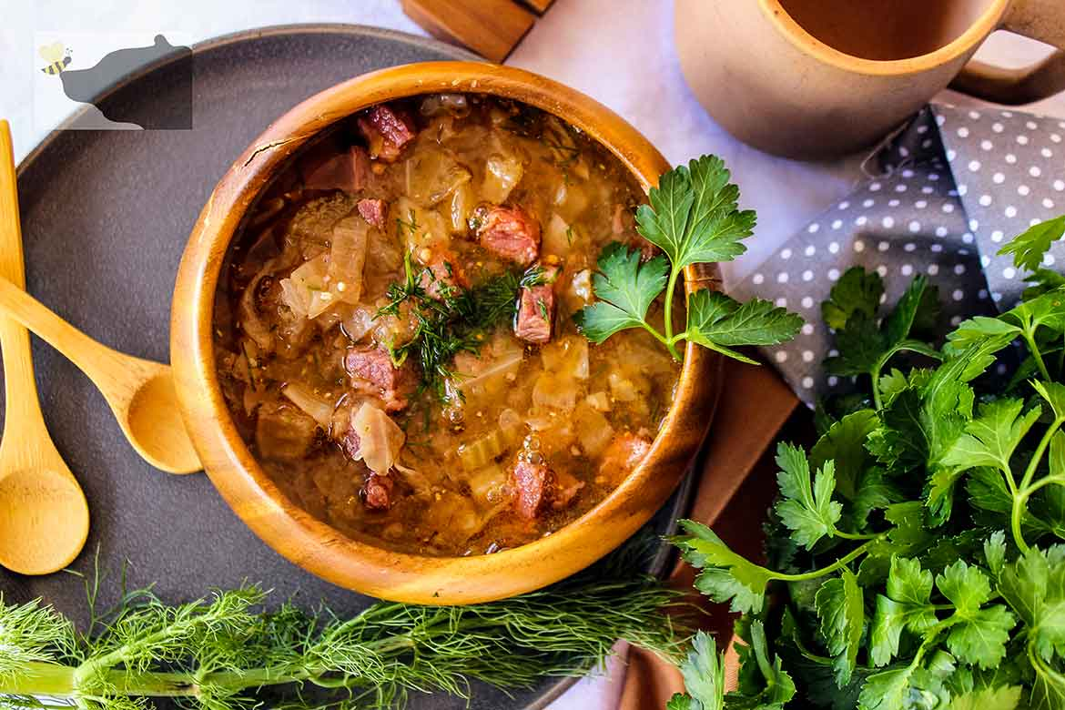 As serving of Corned Beef and Cabbage Soup in a wooden bowl with with spoons to the left and parsley and fennel to the right