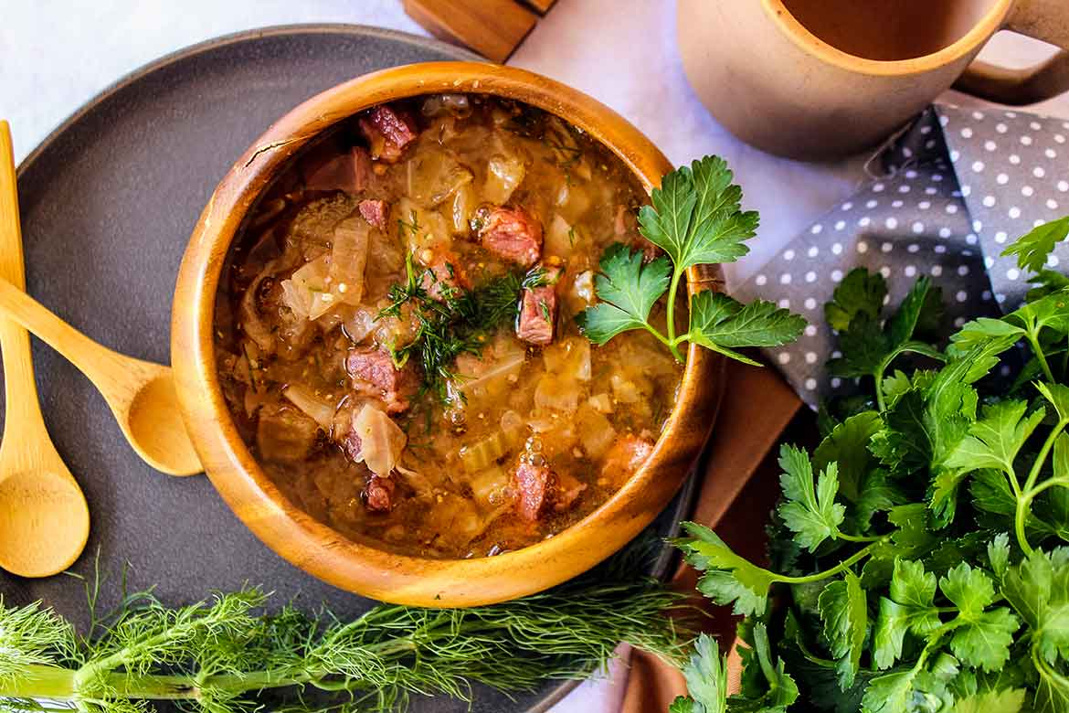 Corned Beef and Cabbage Soup in a wooden bowl with parsley garnish and two wooden spoons to the left