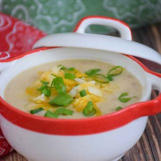 Cheesy Cauliflower Soup with ham in white soup bowl with red trim with cheese and green onion tops sprinkled on top