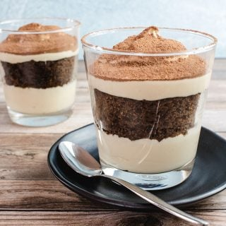 Keto tiramisu in the foreground on a black saucer with a silver spoon on it. There is also another tiramisu in the background.