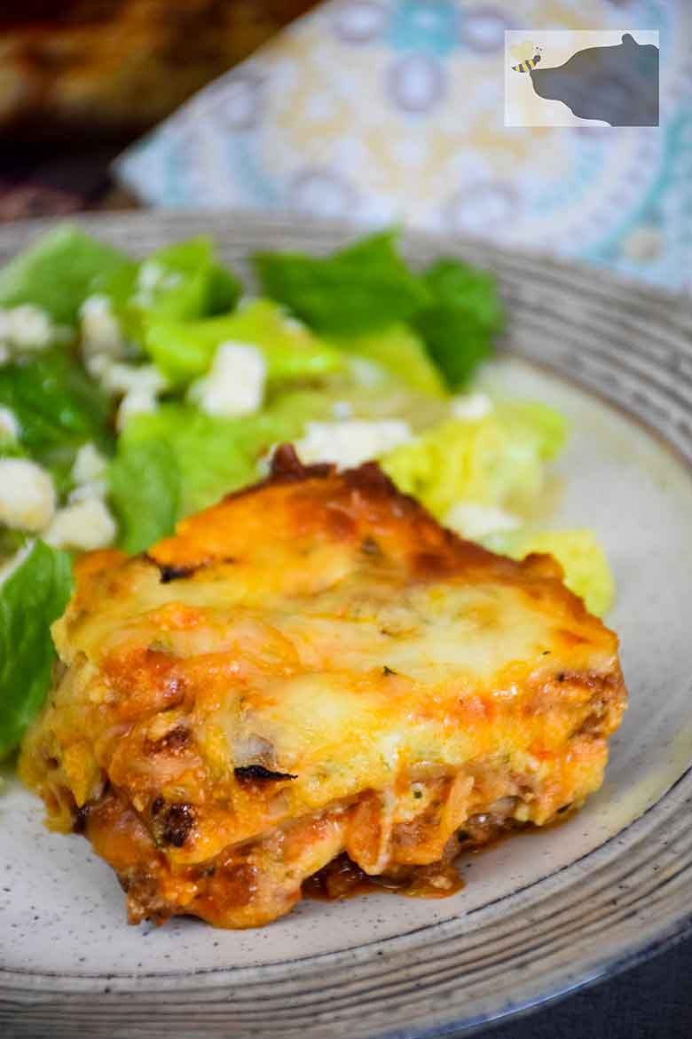 A slice of comfort food on a plate, low carb lasagna serving with a side salad covered in Italian Dressing and Blue Cheese crumbles.