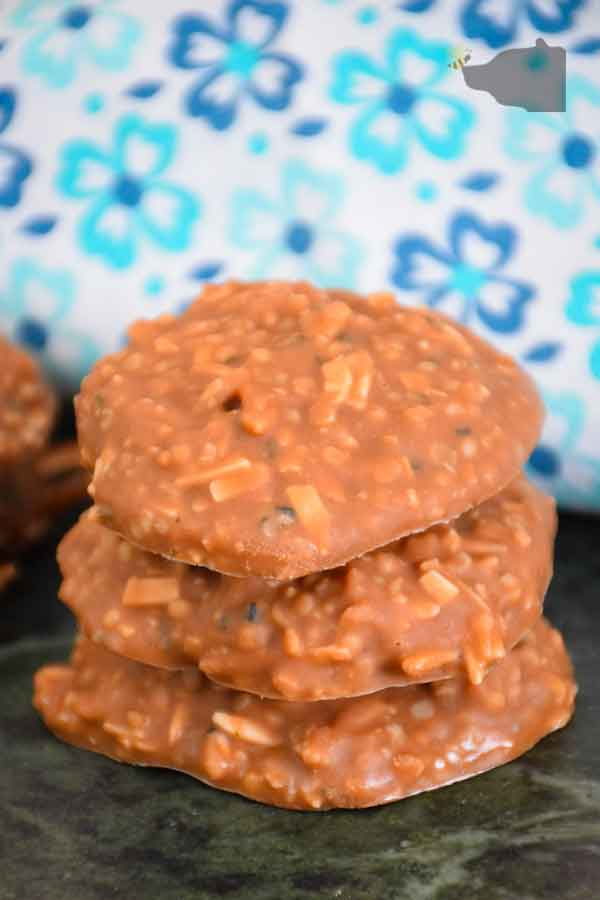 a stack of 3 keto no bake cookies with a stack of two to the left and a blue and white flowered napkin behind the cookies