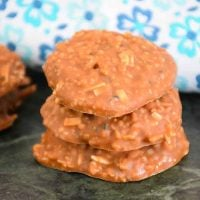 Keto No Bake Cookies also known as Chocolate Peanut Butter Fat Bombs in a stack of 3 with a blue and white napkin in the background