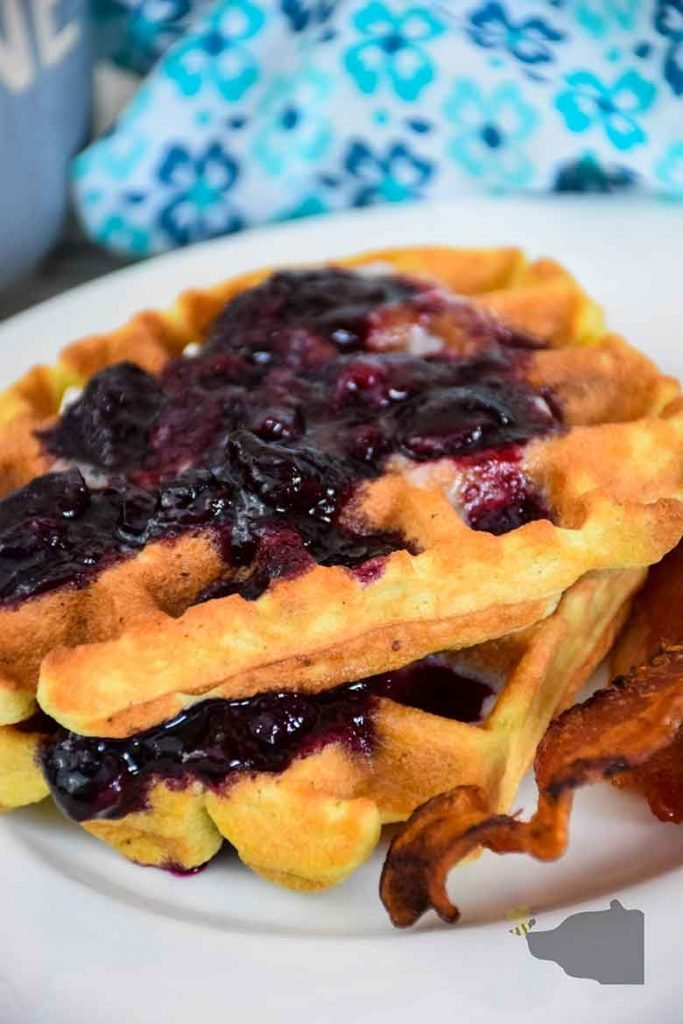 Stack of two blueberry waffles on a white plate with a side of bacon and blue and white napkin