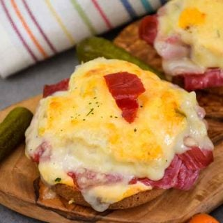 Keto Reuben Open-Faced Sandwich on wooden tray with side of pickles and a striped napkin in the background