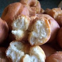 A tray of golden brown homemade buttermilk doughnuts with one deep fried doughnut broken in half to show the inside