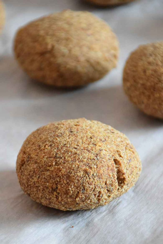 3 baked keto slider rolls on parchment paper on baking sheet