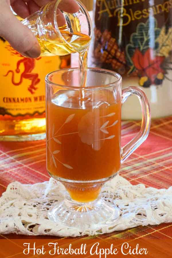 Pouring a shot of cinnamon flavored whiskey into a hot mug of apple cider, pinnable image