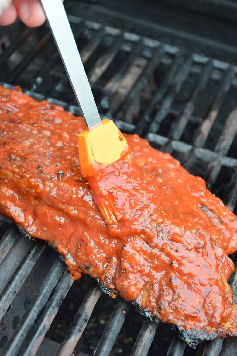 brushing the sugar-free barbecue sauce on the pork back ribs