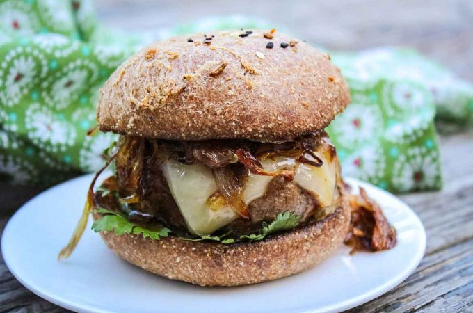 Barbecue Sauce glazed Chipotle Burger topped with cheese and crispy shallots with fresh cilantro on a keto burger bun