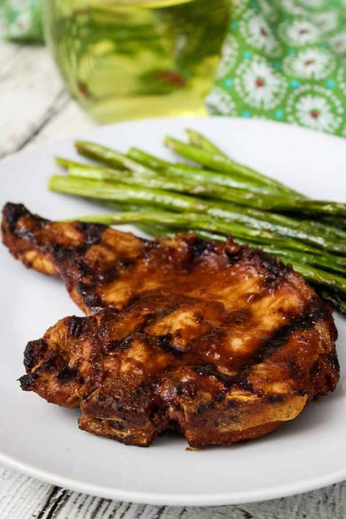 Grilled pork chop with chipotle sauce on a dinner plate with side of asparagus and glass of white wine