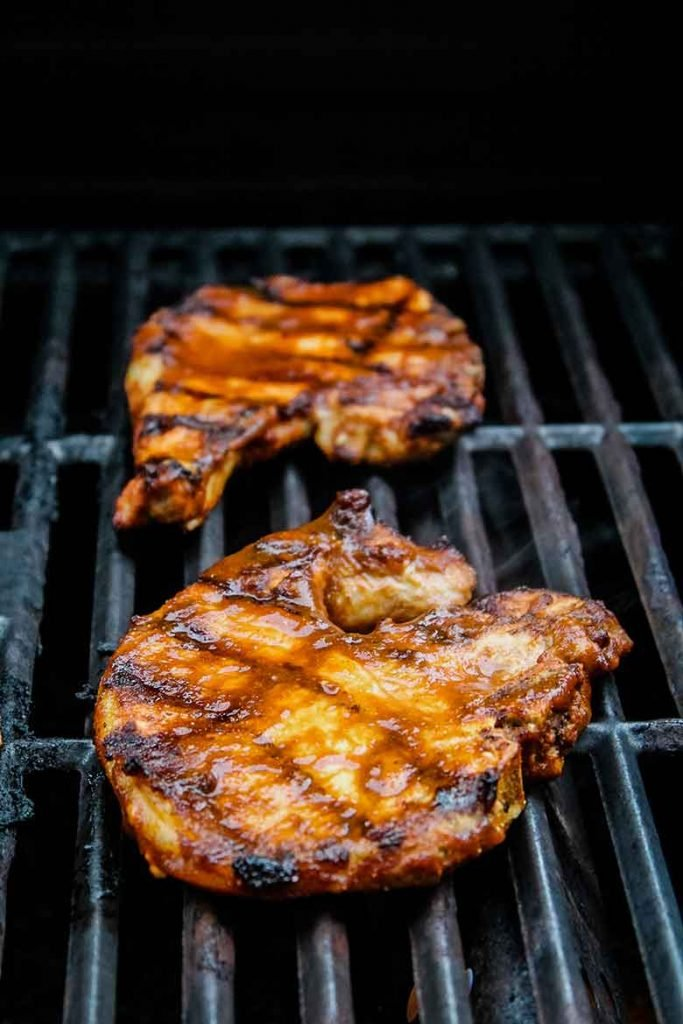 Grilled Pork Chops on the grill with more Chipotle Sauce brushed over top for final cooking