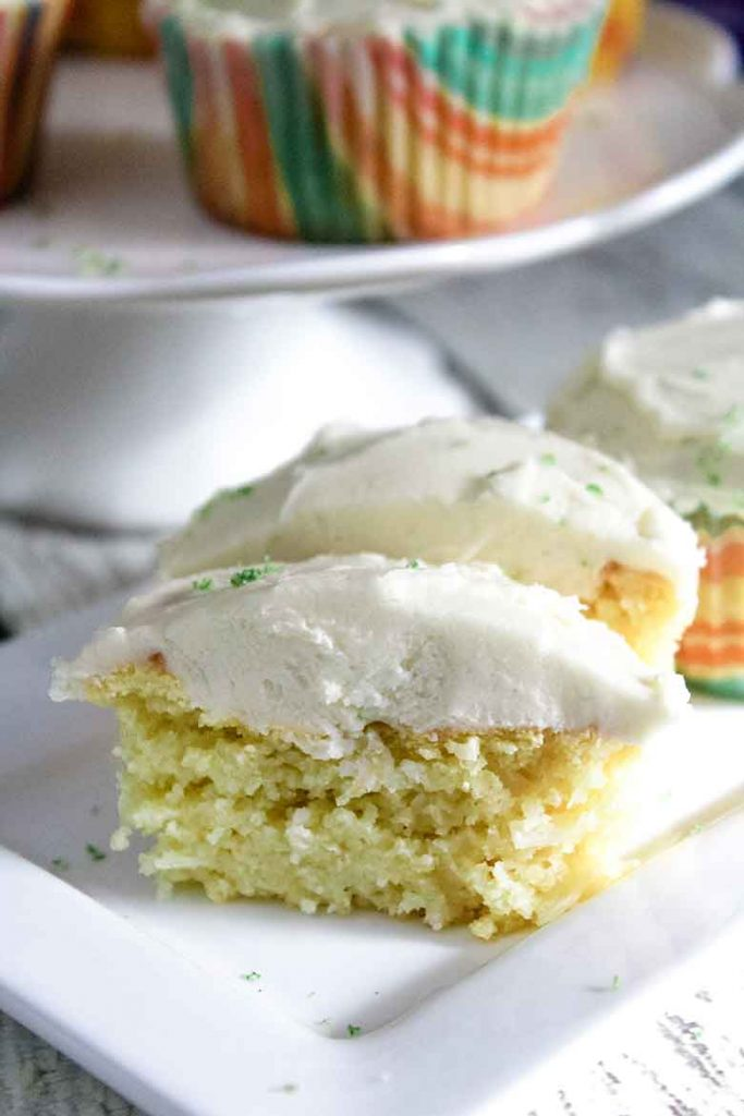 A Keto Coconut Cupcake with Lime Buttercream Frosting cut in half to show the inside texture