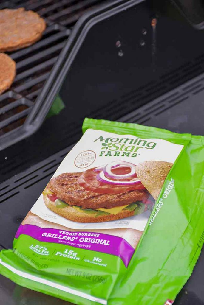 Bag of MorningStar Farms Veggie Burgers on grill side with burgers on the grill