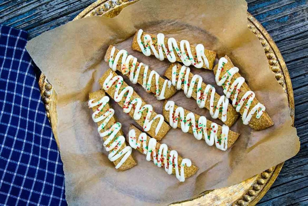Pumpkin Biscotti drizzled with vanilla glaze on parchment lined serving tray
