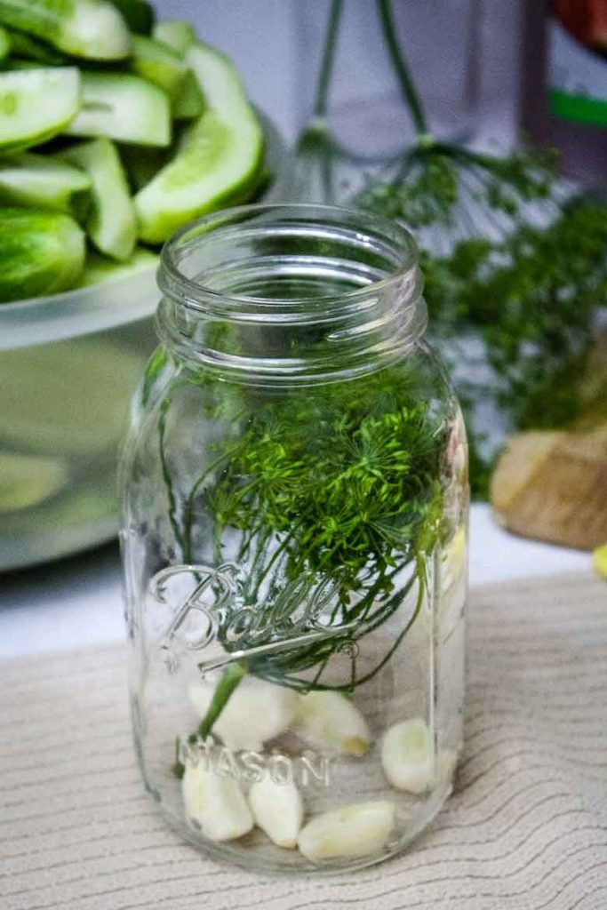 garlic and dill in hot sterilized canning jar
