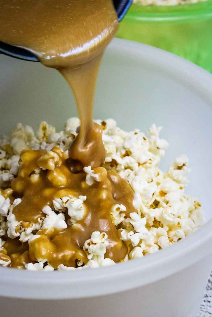 Pouring caramel sauce over top of popped popcorn