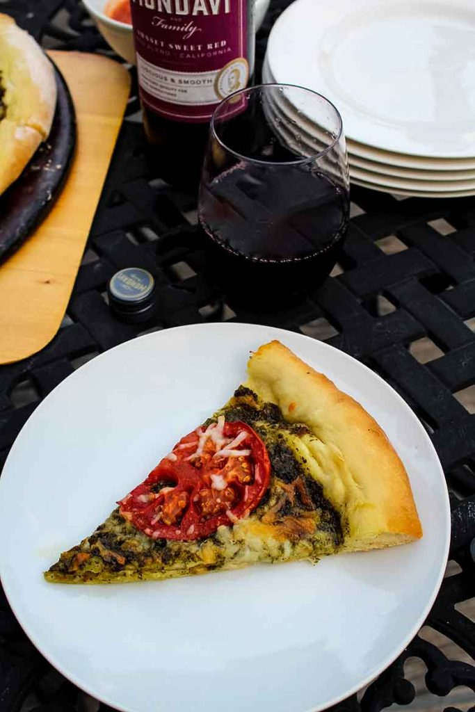A slice of Heirloom Tomato Pizza with Homemade Basil Pesto on a white plate