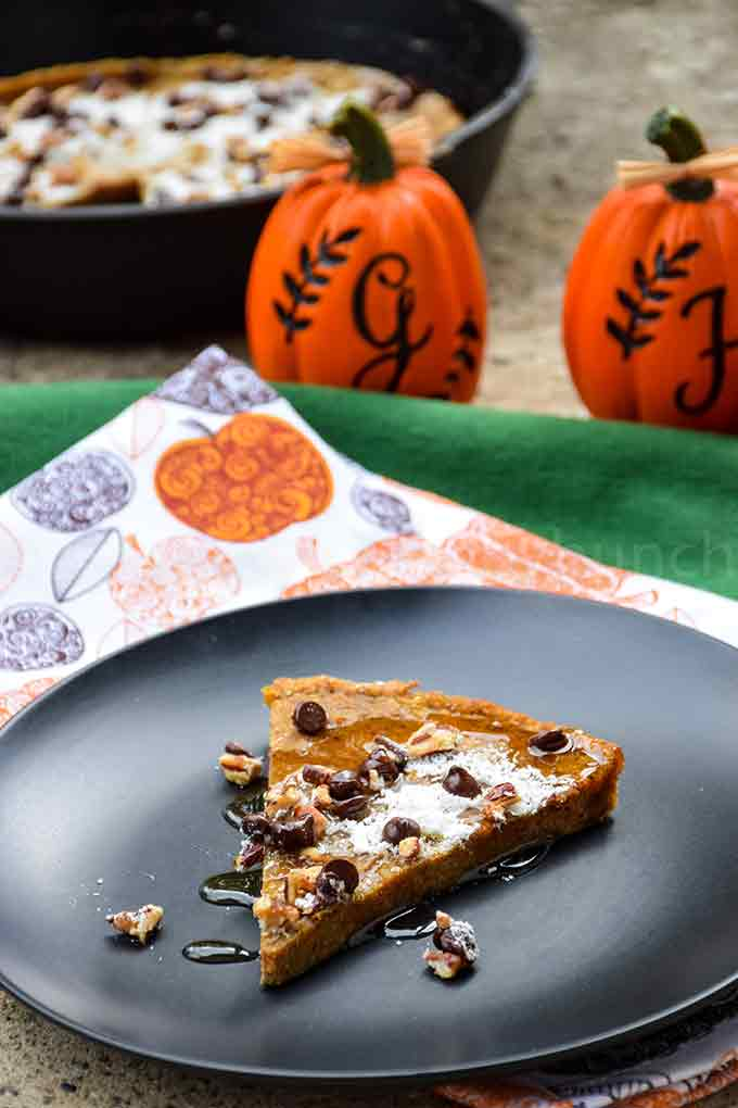 A slice of pumpkin german pancake on a black plate drizzled with sugar free maple syrup