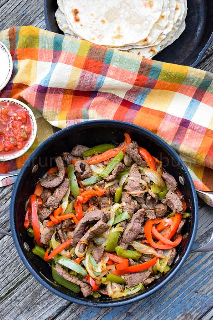 Overhead shot of venison, green peppers, red peppers, onions, in a skillet with a cup of salsa to the left of the skillet and a multi colored plaid orange napkin in the background.