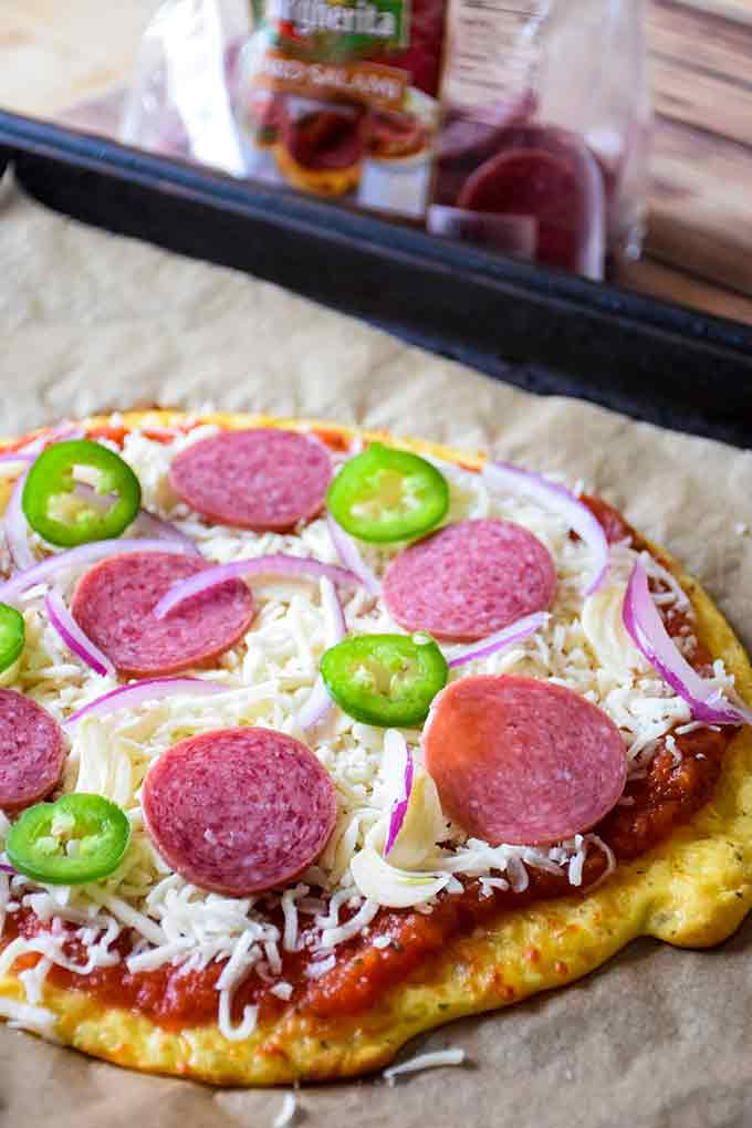 a dressed salami pizza before the final baking