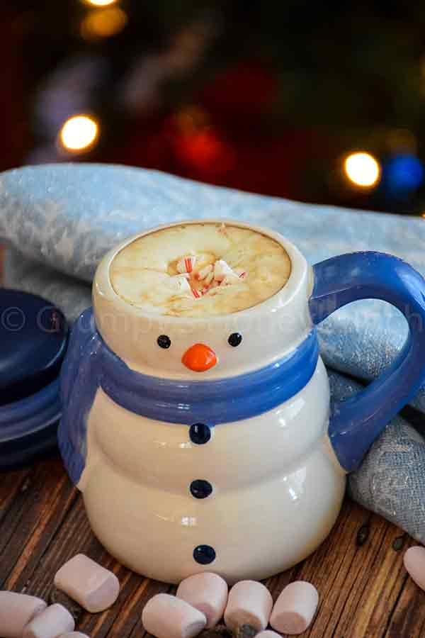 creamy hot cocoa in a snowman mug with crushed sugar-free peppermint on top