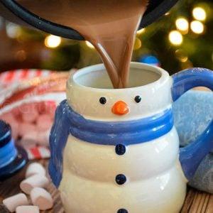 Creamy Hot Cocoa being poured into a snowman mug