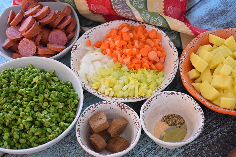 Ingredients for slow cooker soup recipe, split peas, bouillon cubes, herbs, diced potatoes, celery, onion, carrots, and slices of kielbasa sausage.