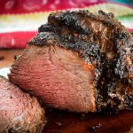 Air Fryer Roast Beef on cutting board with slices cut from the roast
