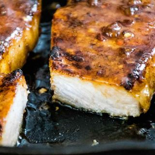 Honey Garlic Pork Chops in the skillet with a piece of pork cut from the cooked product