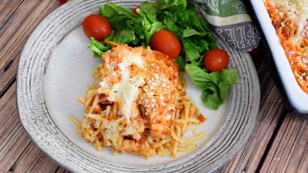 overhead view of chicken parmesan casserole with a side salad
