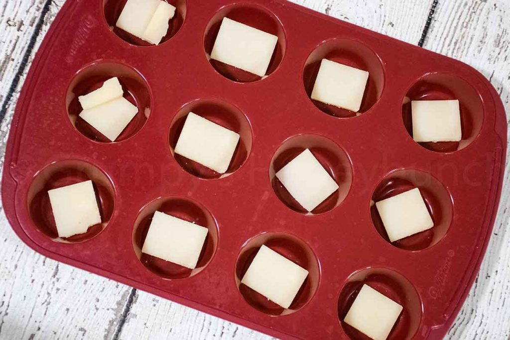 slices of cheese in the silicone mini muffin pan