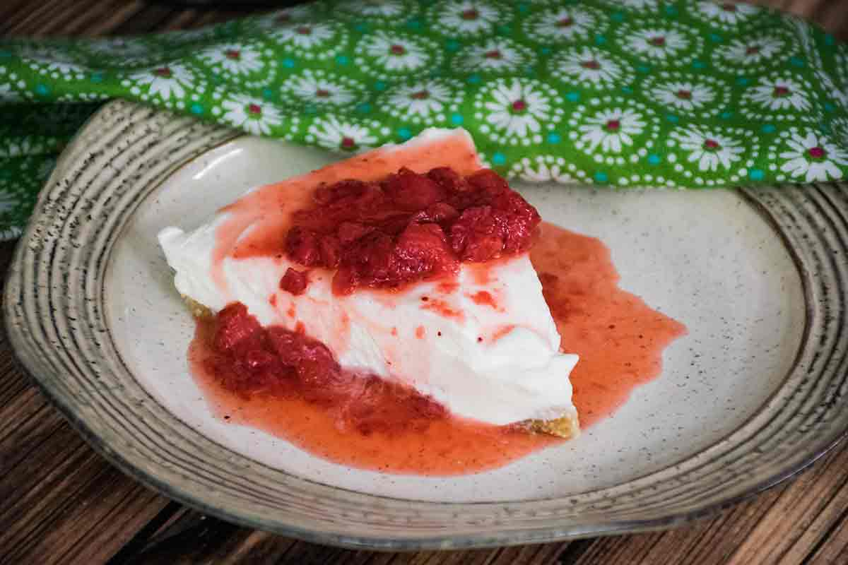 A serving of Keto No Bake Cheesecake on a plate with a green napkin in the background