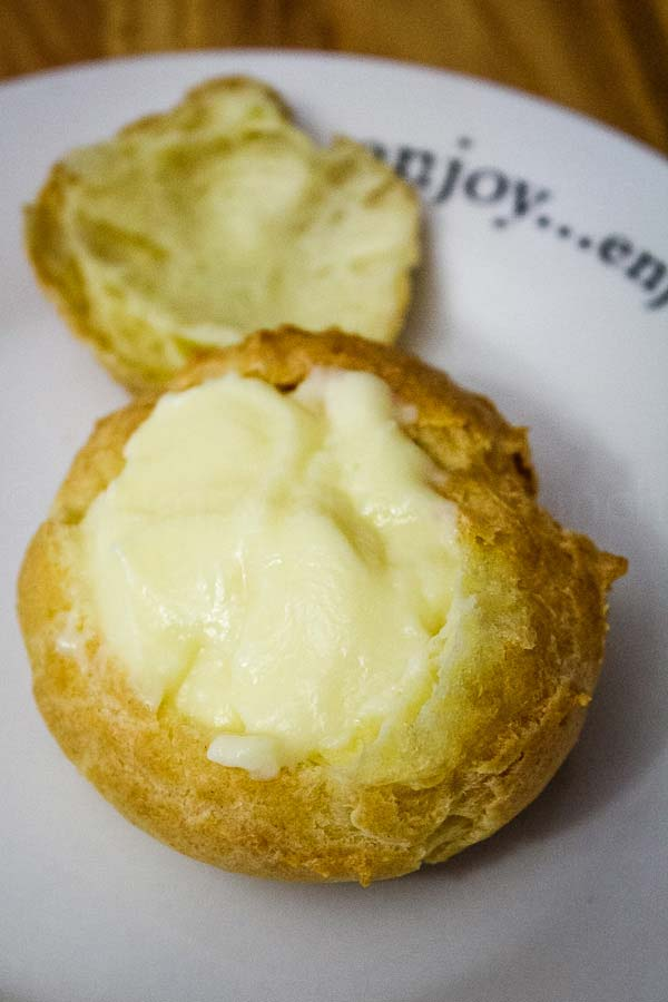 Baked cream puff with top removed and vanilla pastry cream in the puff