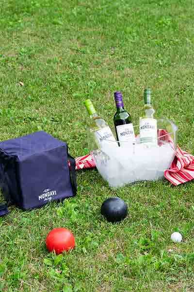 A bocce ball set with a chilling bucket full of ice and 3 bottles of wine