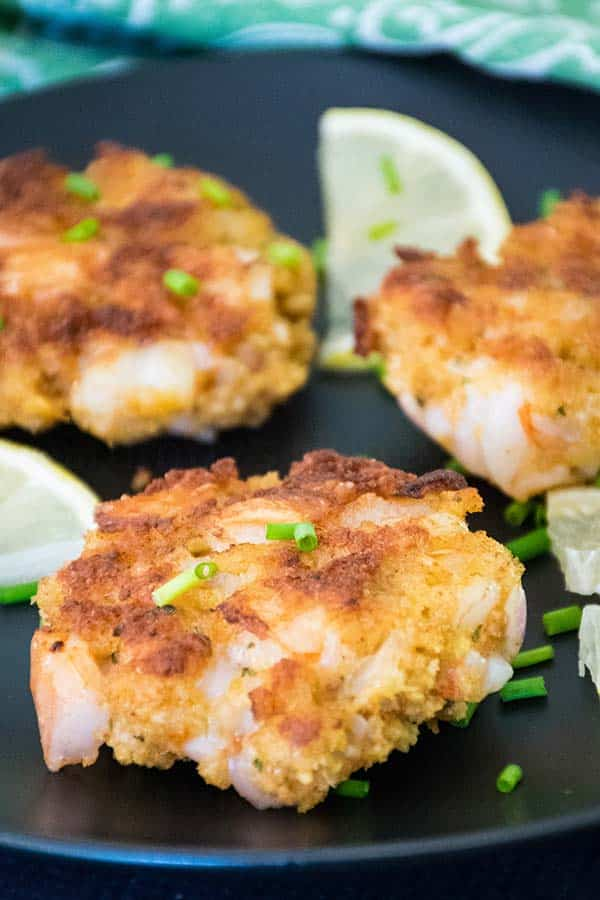 Chipotle Spiced Fried Shrimp Cakes on a black plate with lemon slices and chives